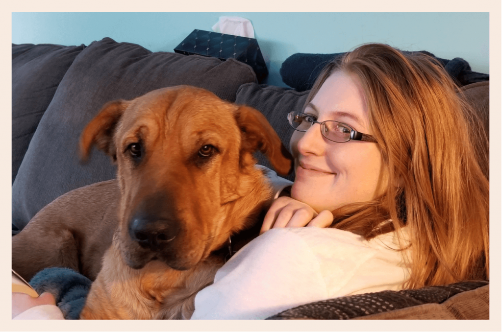 woman sitting on the couch, looking back towards the camera, with a large dog sitting on her lap.