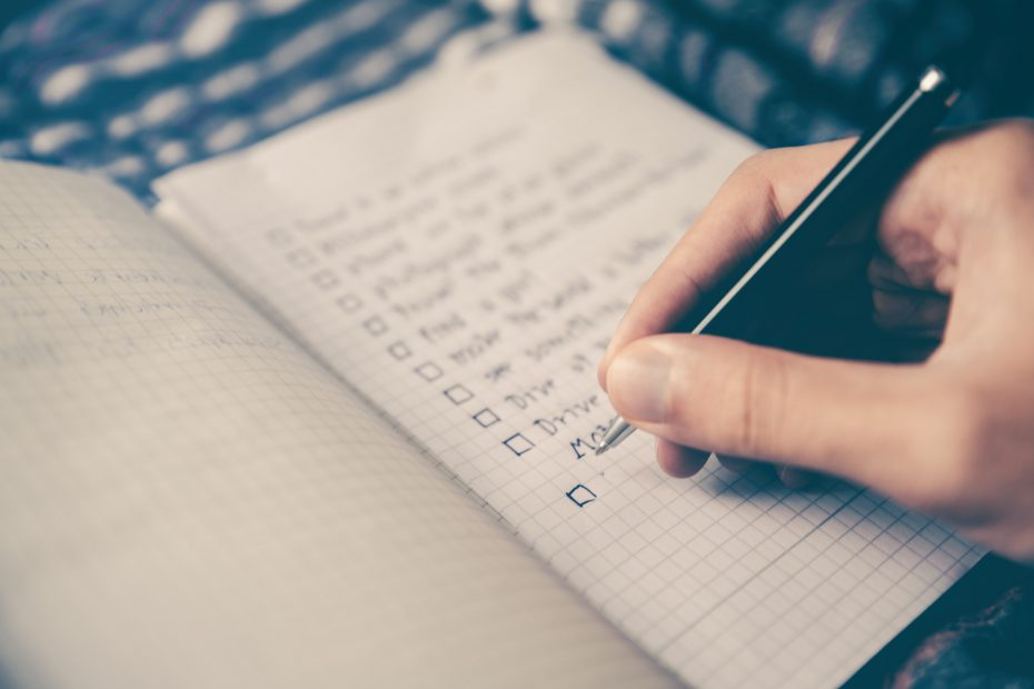 person writing a goal list in a notebook